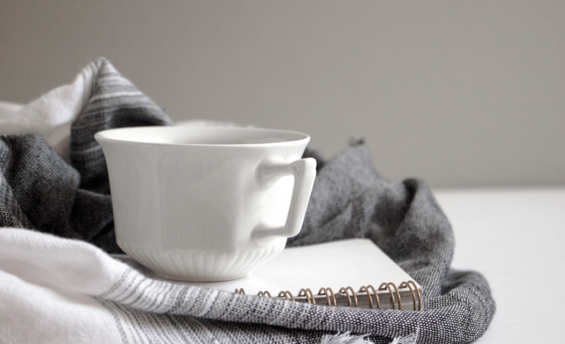 Picture of notebook and white teacup on top of a grey scarf
