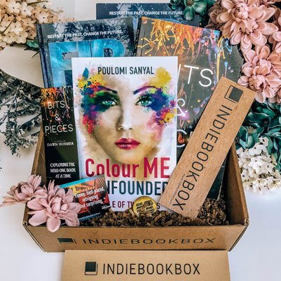 Bookstagram picture and ad of the Indie Book book, a box filled with 4 indie books, bookmarks and a pin surrounded by pink and blue pastel flowers