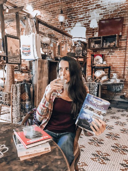 How To Start A Book Review Blog Niche With The Uncorked Librarian--a brunette woman--Holding the book Names for the Sea and a glass of white wine in an antique book bar
