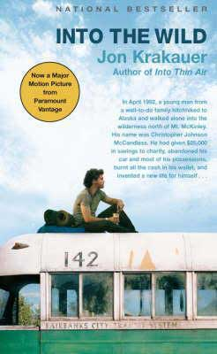 Into the Wild by Jon Krakauer book cover with young brunette man sitting on top of an old bus with a backpack
