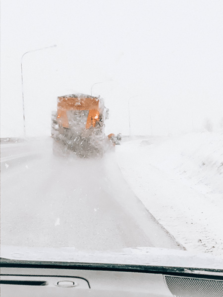 driving in Iceland in winter snow as yellow truck clears the road