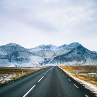 How To Better Prepare For Driving In Iceland In Winter with snowy road and Icelandic mountains