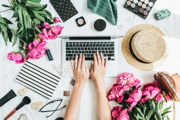 LLC For Bloggers Guide Why & How Register Blog As Business with person typing on laptop, straw hat, pink flowers, glasses