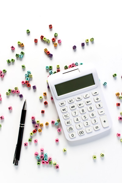 LLC For Bloggers Self Employment Taxes with white calculator, pen, and colorful letters
