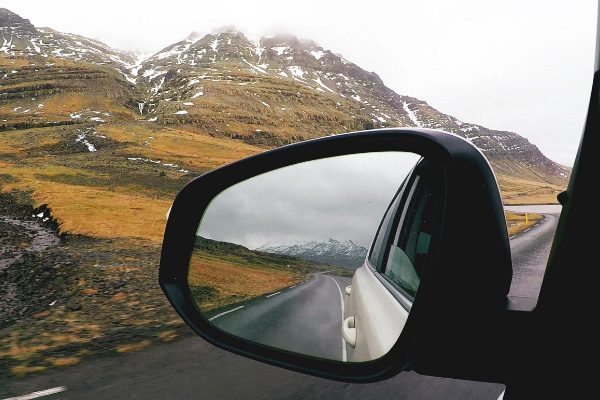 Renting A Car Driving In Iceland In Winter with Icelandic landscape in rearview mirror of car