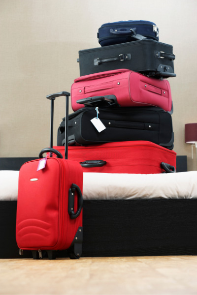 Self Driving In Iceland Pro Bring More Luggage with stack of red, black, and pink suitcases on a bed