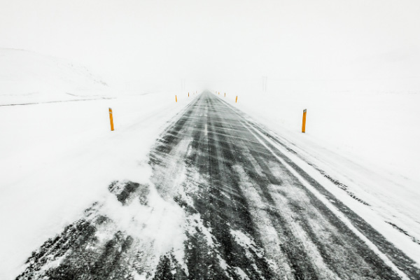 Strong wind driving in winter Iceland with road covered in blown snow