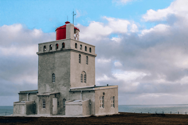 Dyrhólaey Lighthouse in Iceland  with gray lighthouse and clouds