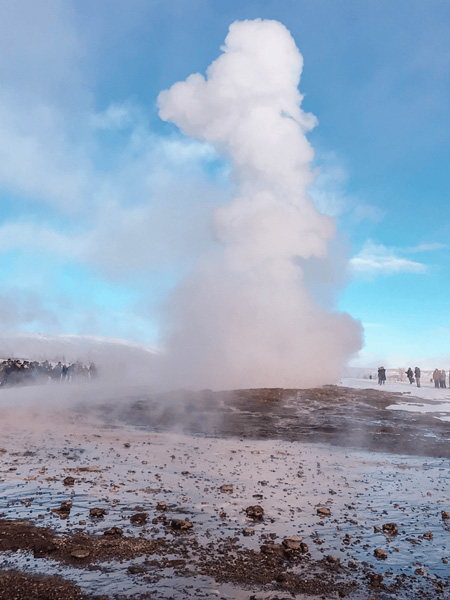 Geysir in Iceland with steam and water shooting from the ground