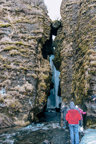 Gljufrabui Waterfall South Iceland with crack between rocks and waterfall in between along with people looking in