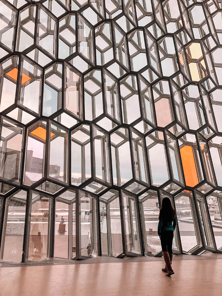 Harpa in Reykjavík Iceland with brunette woman standing in front of geometric stained glasses windows