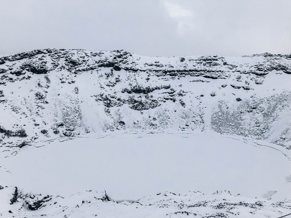 Kerid Crater Iceland in winter with 7-day itinerary and snow; Kerid crater is a hole covered with frozen water and white snow