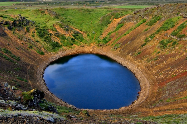 Kerid Crater Iceland with blue water in a hole surrounded by land