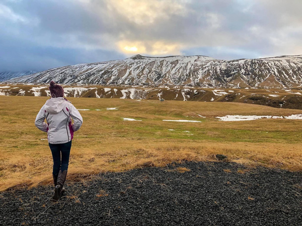 Week In Iceland Hella Road Trip Stop with brunette white woman in a white winter coat standing on  green grass looking at a snow covered mountain