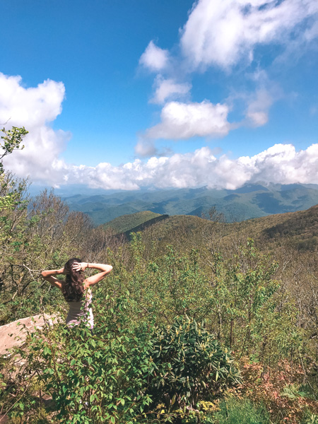 Living In Asheville Pros Hiking with brunette white woman looking out at Blue Ridge Mountains at Craggy Gardens
