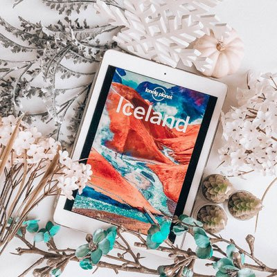 bookstagram flat lay example two with ereader showing a Lonely Planet Iceland travel guide, white and turquoise flowers, and tree candles
