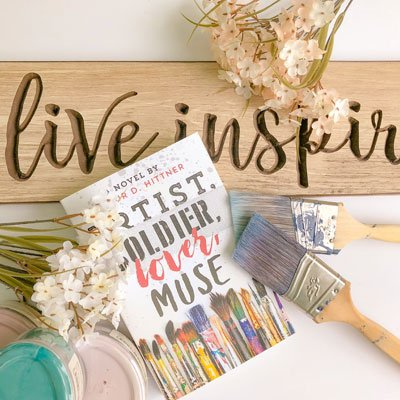 How to start a bookstagram flat lay example one with Artist, Soldier, Lover, Muse, paint jars, paint brushes, and a wooden live inspired sign
