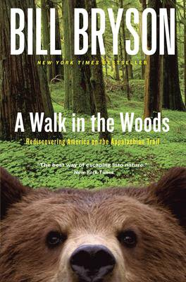 A Walk In The Woods By Bill Bryson book cover with green woods and brown bear face looking at the reader