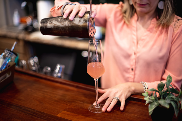 How to make a blackberry smash with woman in a pink blouse pouring pink liquid into a glass from a shaker with a strainer on a bar top