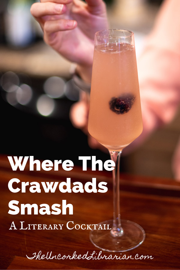 Where The Crawdads Smash Literary Cocktail with champagne flute filled with pink blackberry smash and a woman in a pink blouse dropping in a blackberry