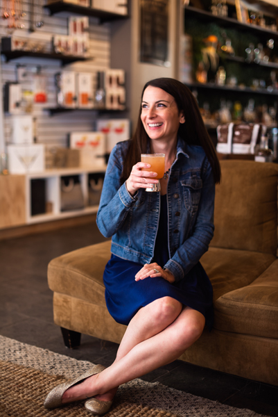 White, brunette woman drinking a peach and gin cocktail on a brown sofa at Cultivated Cocktails in Asheville, NC