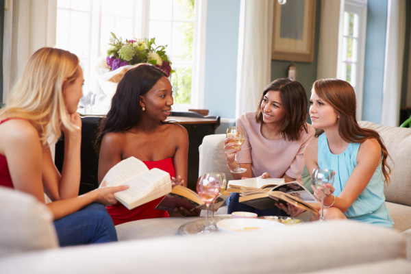Blog Post Ideas Book Club with four women sitting on a couch drinking wine and holding books