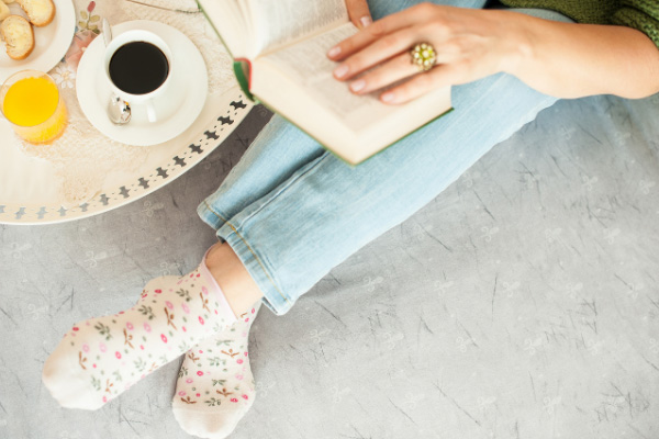 Book blog ideas like how to read more with person sitting on the floor with book and cup of coffee