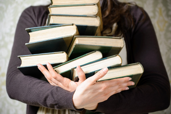 Book Blog Post Book Hauls with person holding an uneven stack of books