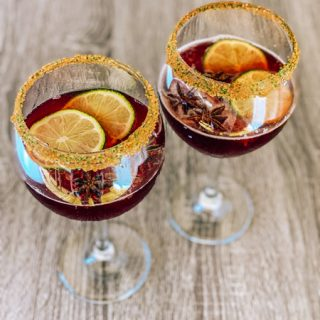 Cheerwine Cocktail bourbon with two large wine glasses filled with Cheerwine and lime garnish