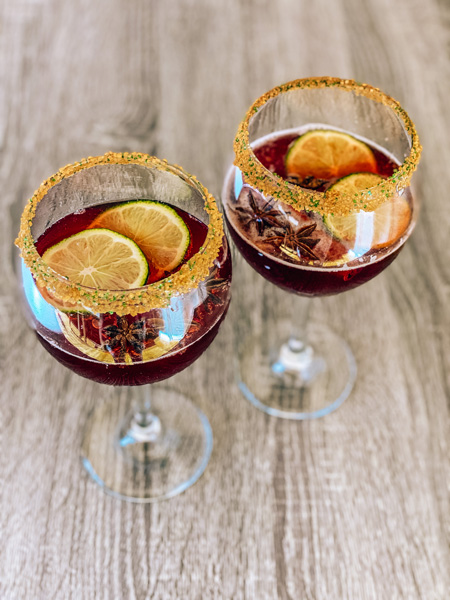 Cheerwine Cocktail Bourbon Recipe with two large wine glasses filled with Cheerwine Holiday punch and lime garnishes