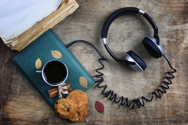 Controversial Book Blog Post Ideas Audiobooks with black headphones attached to a green book