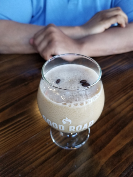 Coffee Mead Cocktail with glass filled with coffee drink and floating coffee beans with person in blue shirt's arms in the background