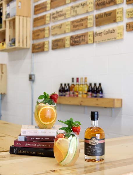Lady Jane Literary Mead Cocktail with two cocktails, stack of Jane Austen books, and bottle of mead with meadery taproom in background