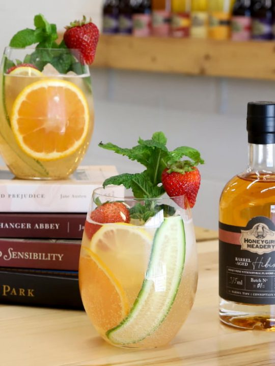 Mead Cocktails Recipes with two cocktails, bottle of Honeygirl Meadery Mead, and stack of Jane Austen books