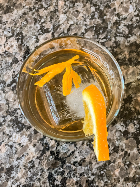 Orange Old Fashioned Mead Cocktail with shot from top of glass with square ice cube and orange zest and slice garnish