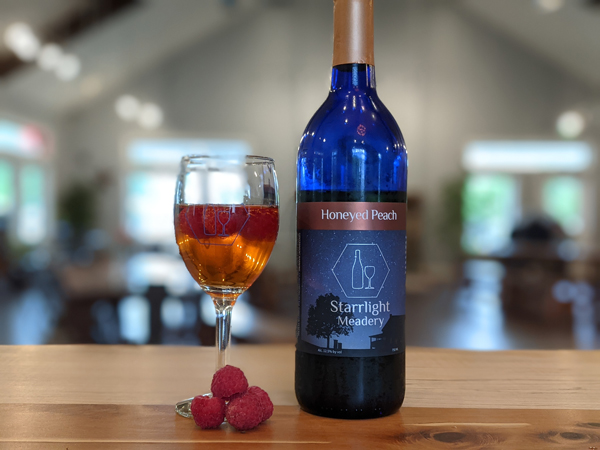 Raspberry Peach Sangria Mead Cocktail with raspberries and bottle of Starrlight Mead
