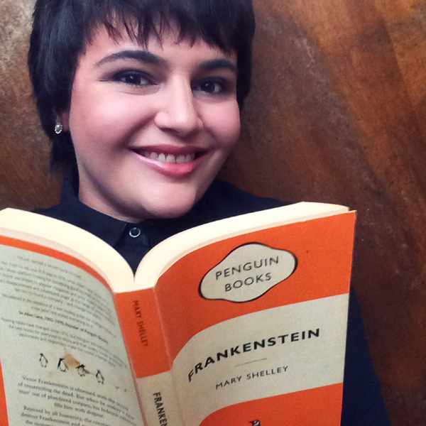 Sheree from Keeping Up With The Penguins, short black hair woman holding an orange stripped book, Frankenstein