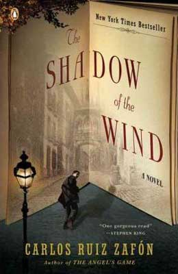 The Shadow of the Wind by Carlos Ruiz Zafón book cover with street lamp and person walking stealthily away with buildings in background