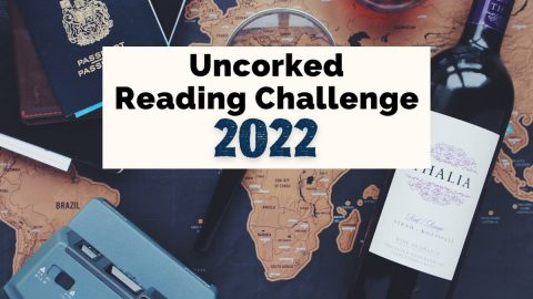 Uncorked Reading Challenge 2022 with bottle of wine, passport, blue old fashioned camera, and maps